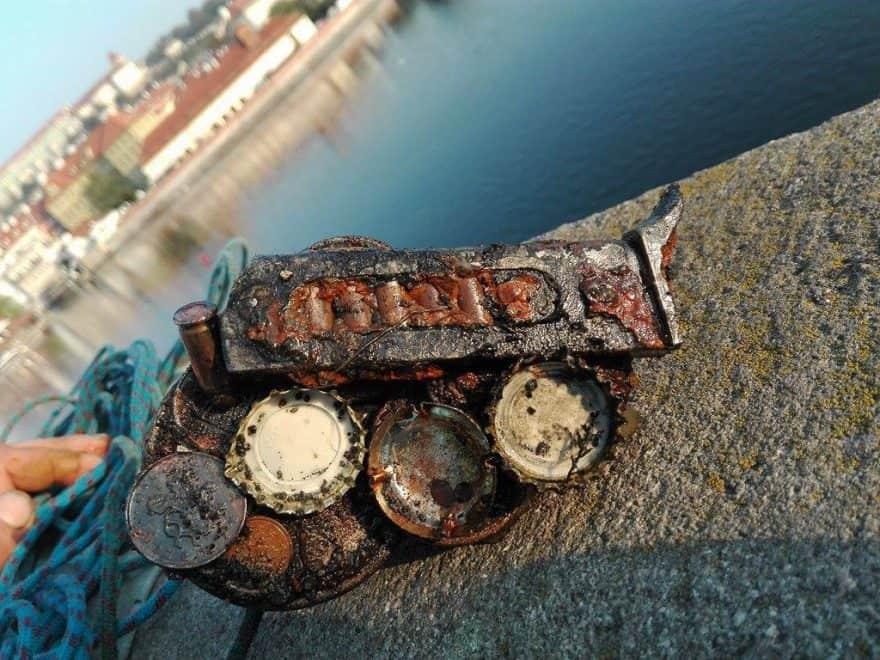 Zásobník a vrchnáky od piva na magnete pri brehu Vltavy