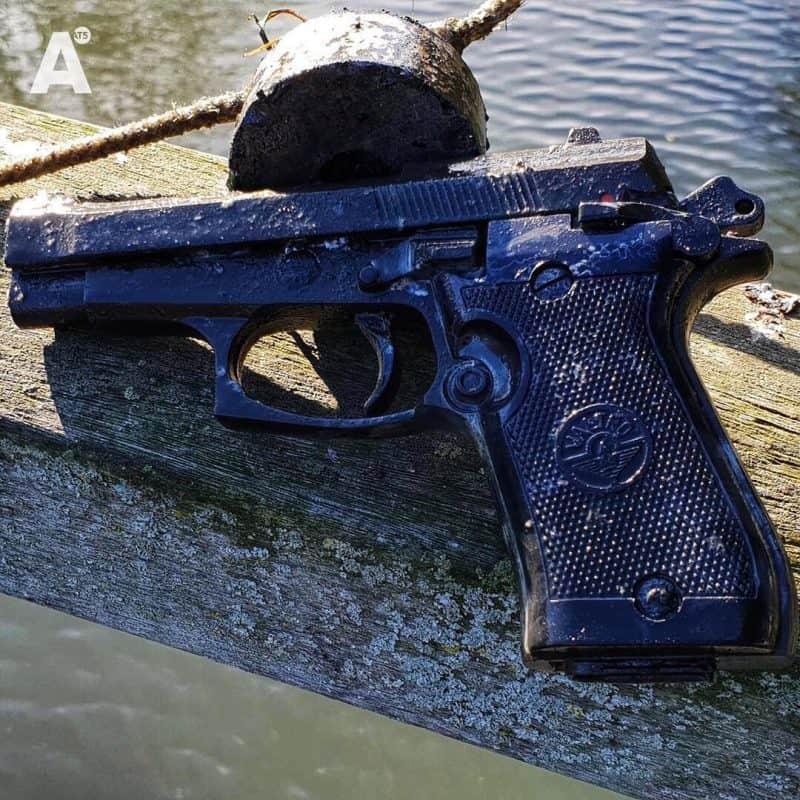 Pištoľ a fishing magnet na betónovom múre