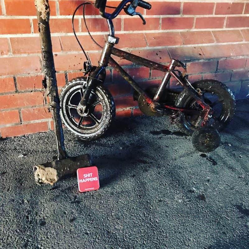 kladivo a detský bicykel opretý o múr