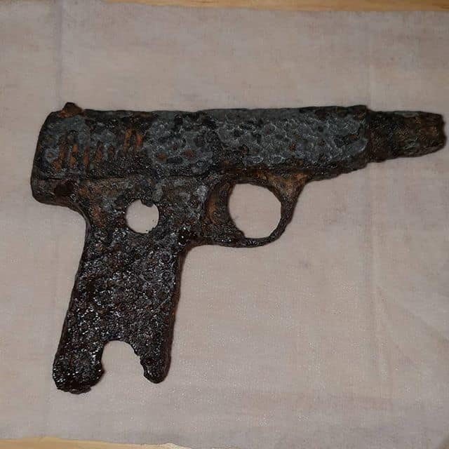 rozpadnutá, hrdzavá pištoľ