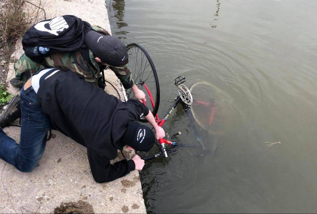 Dvaja lovci pokladov ťahajú bicykel z rieky