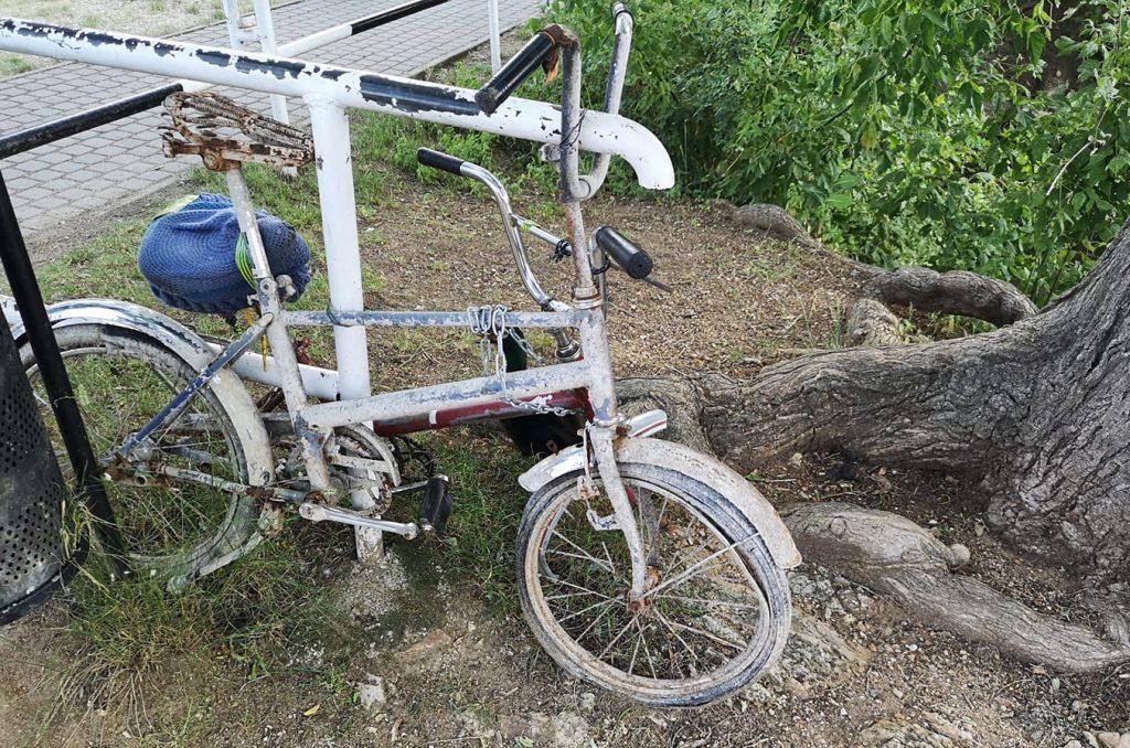 Skorodovaný bicykel opretý o zábradlie