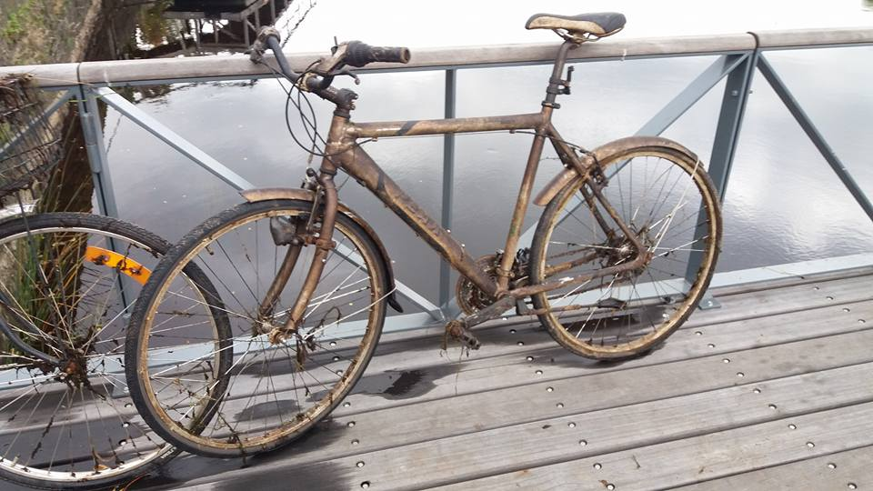 Bycikel, ktorý práve lovci vytiahli na breh