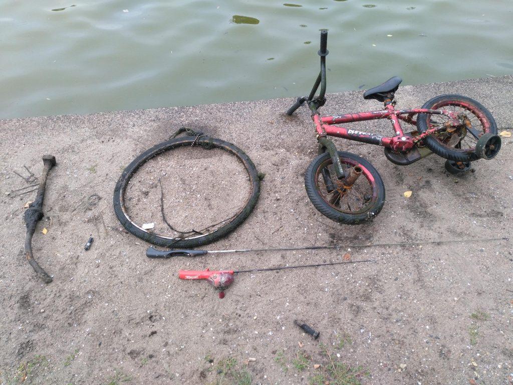 Detský bicykel, koleso a udice na kamennom brehu