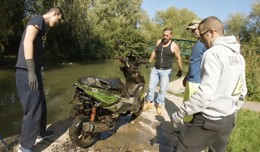 Štyria magnet fisheri okolo motorky, ktorú našli v potoku