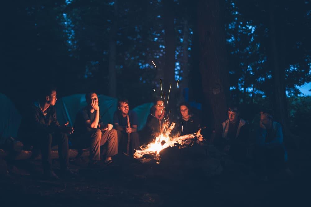 Ľudia v tábore sediaci okolo ohňa